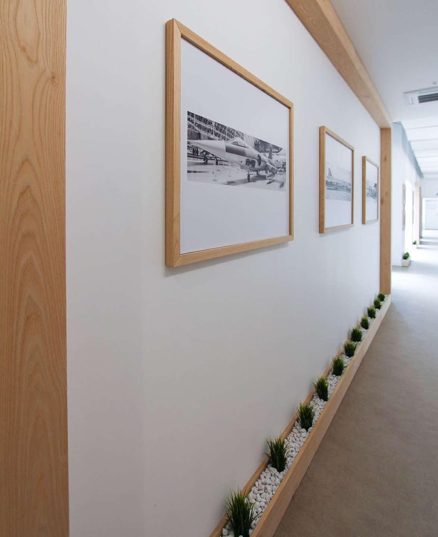 Photo prise sur un des grands encadrements réalisés sur-mesure par les menuisiers avec une petite rigole de galets au sol dans laquelle sont plantées des petites plantes vertes artificielles
