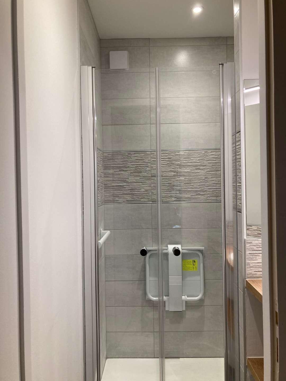 La douche est équipée d'un siège PMR